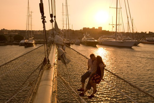 Couple in Bowsprit Net, Star Flyer, sunset over the Rhodes Harbor, Rhodes, Dodecanese Islands, Greece : Stock Photo