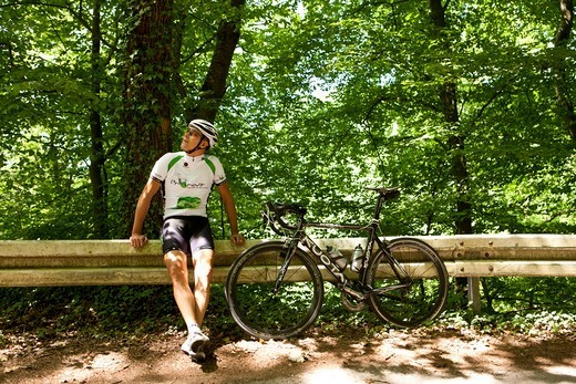 Bicycle racer leaning against guardrail, Bergisches Land, North Rhine-Westphalia, Germany : Stock Photo