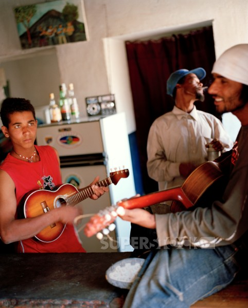 Father, sun and cousin playing music at Casa Ramiro, Cha das Caldeiras, Island of Fogo, Ilhas do Sotavento, Republic of Cape Verde, Africa : Stock Photo