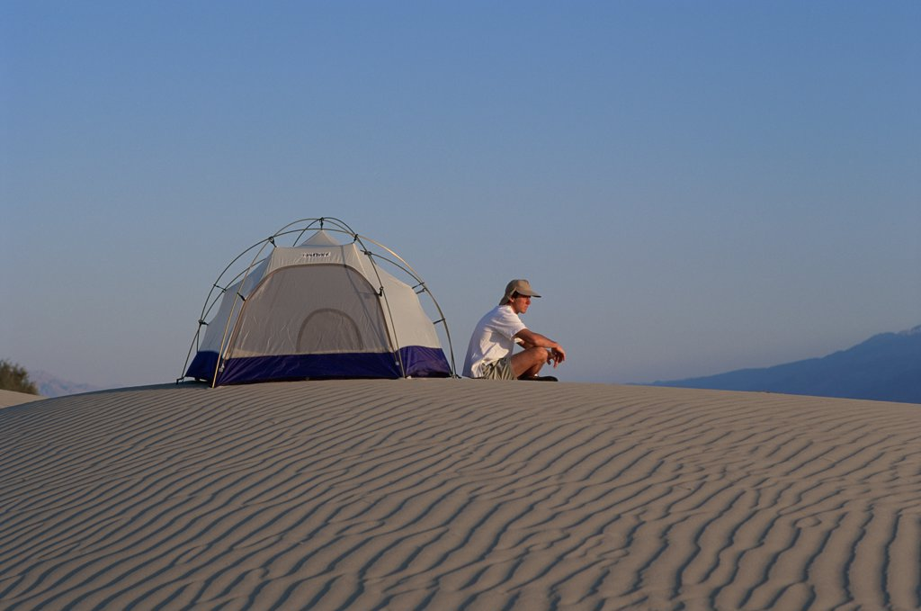 Stock Photo: 445-3563A Man sitting outside a tent on a sand dune in Death Valley National Monument, California, USA