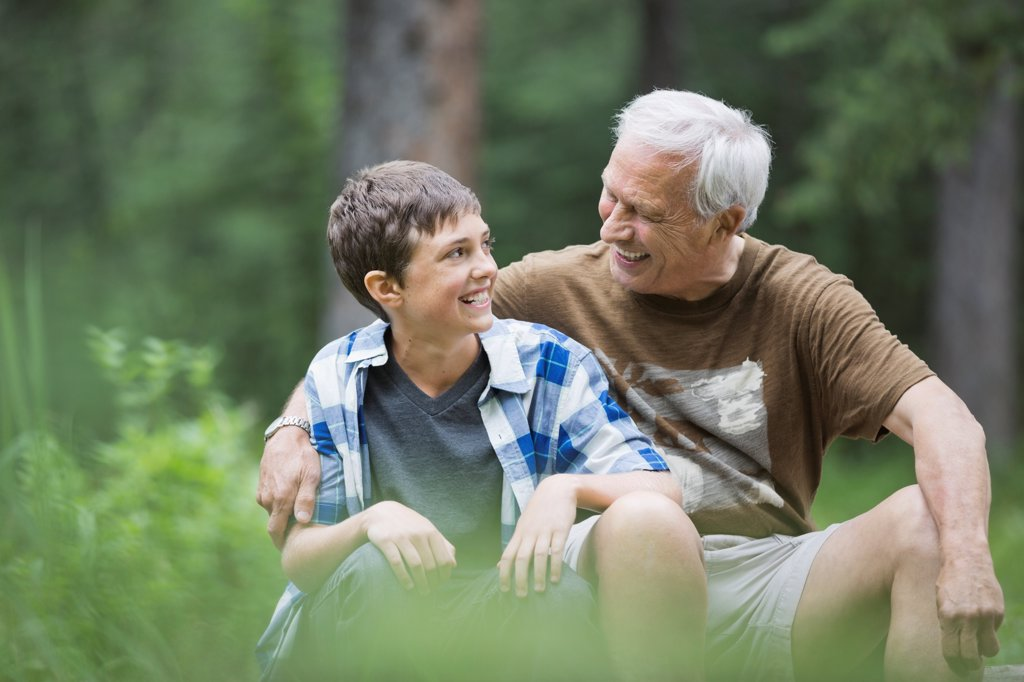Stock Photo: 4451R-5285 Happy grandfather and grandson sitting outdoors