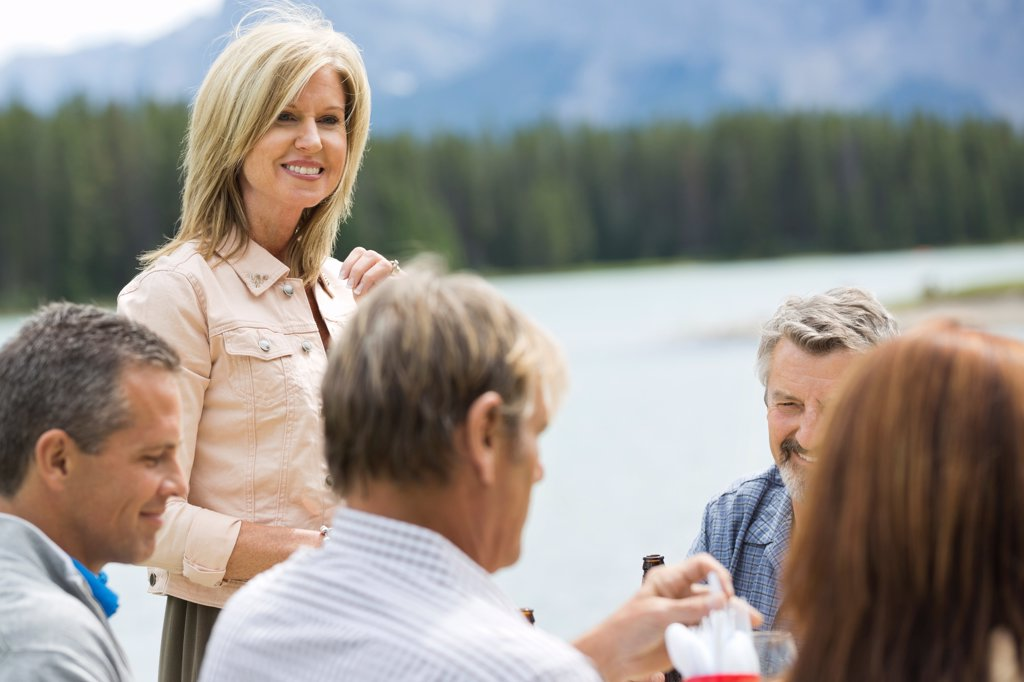 Mature woman socializing with friends outdoors : Stock Photo