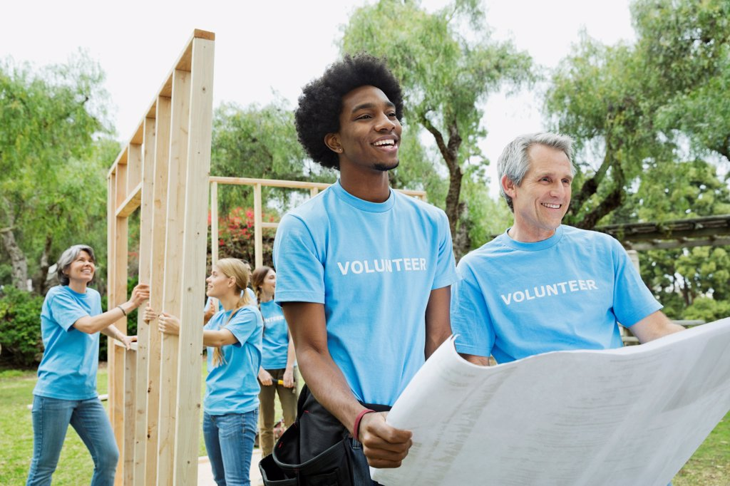 Men holding blueprint with volunteers constructing wooden frame in background : Stock Photo