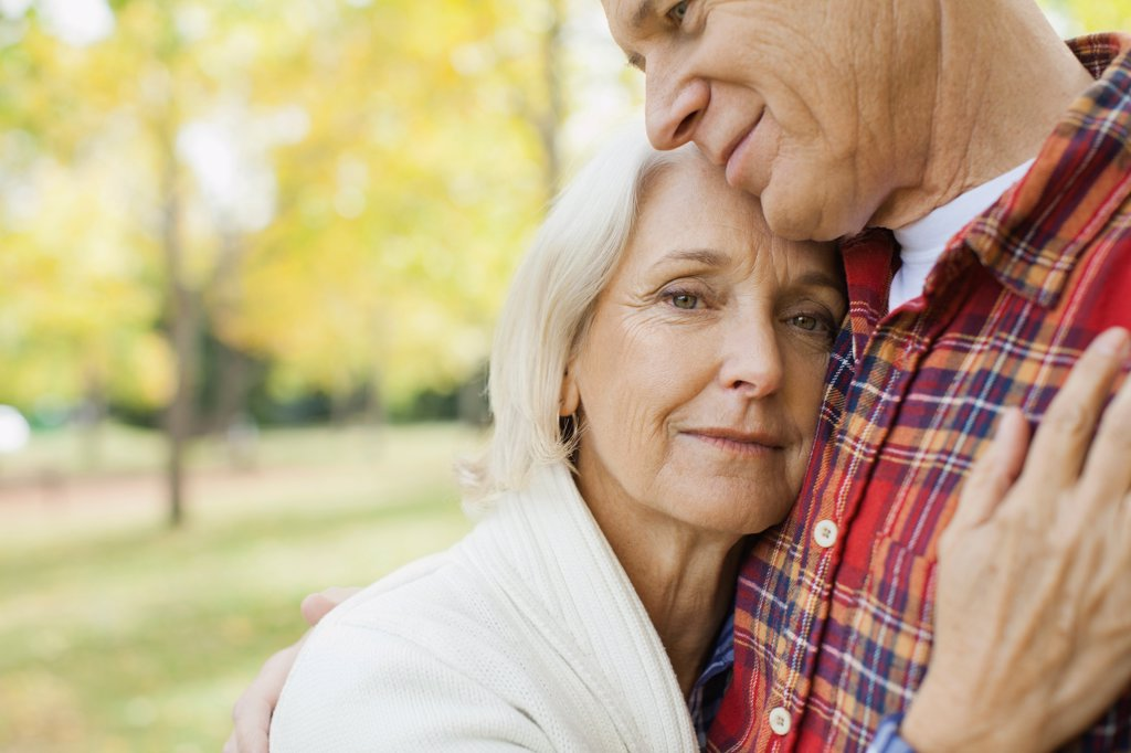 Portrait of affectionate mature woman with man at park : Stock Photo