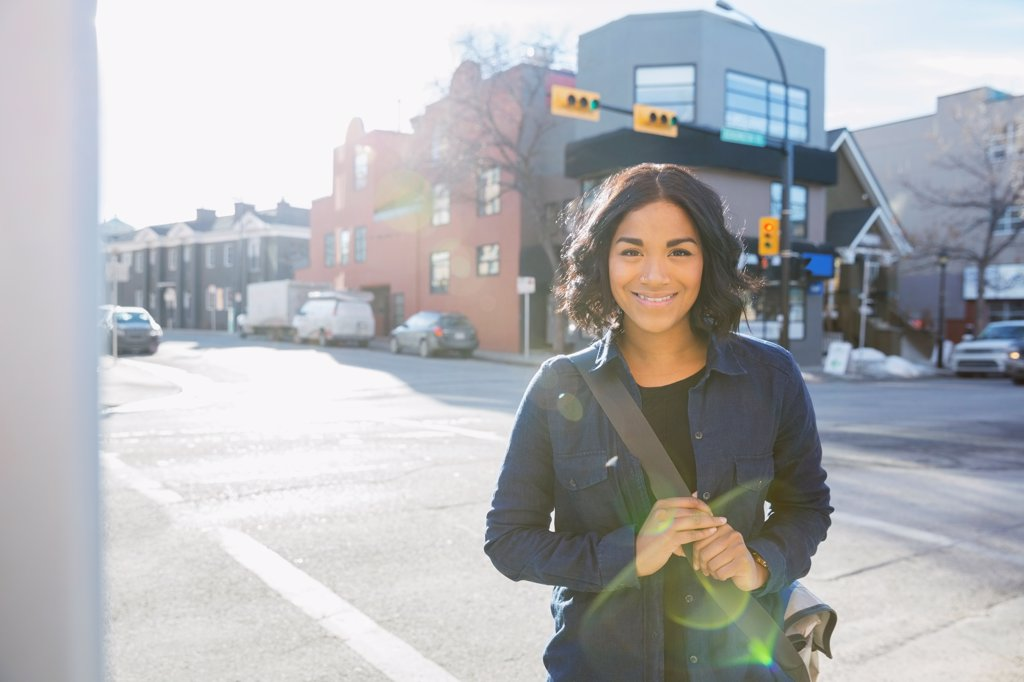 Stock Photo: 4451R-9810 Portrait of smiling woman standing on city street