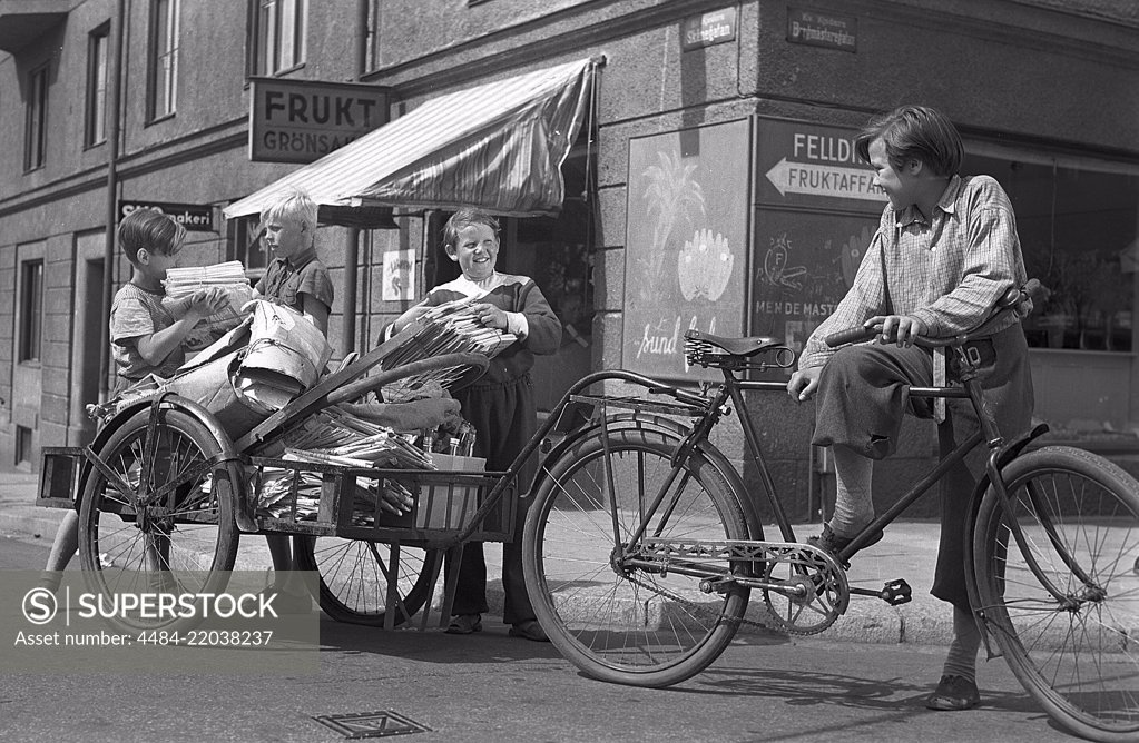 Stock Photo: 4484-22038237 1940s children. Scene from the Swedish movie Kvarterets olycksfågel 1947. The boys are working extra as bicycle messangers and doing deliveries to earn extra money. Sweden 1947