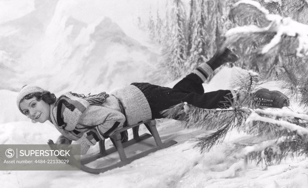 Stock Photo: 4484-22133029 Woman on a sledge 1930s. The young actress Isa Quensel , 1905-1981, during the filming of the movie Kärlek måste vi ha.