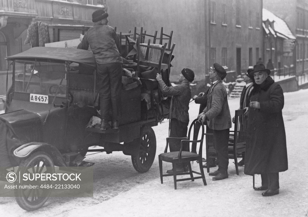 Stock Photo: 4484-22133040 Moving in the 1920s. It's a winter day when the furniture and other things are loaded onto a truck in the central of Stockholm to move to a new location. Sweden 1920s