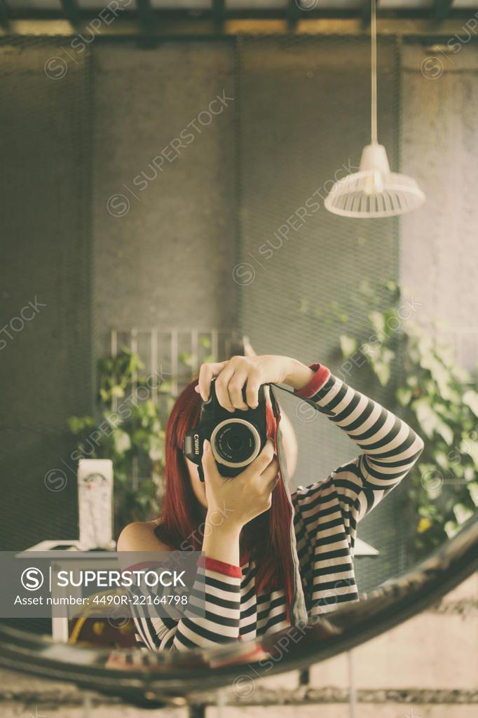 Stock Photo: 4490R-22164798 The girl camera mirror self portrait