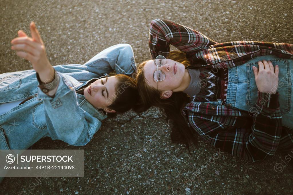 Stock Photo: 4491R-22144098 Women couple lying on road