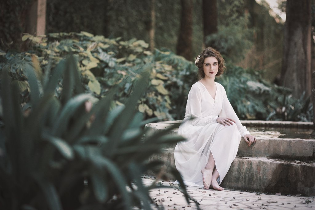 Stock Photo: 4491R-22146352 Attractive young woman in white clothes sitting at concrete pond in the park.