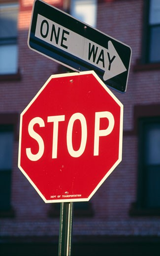 Stock Photo: 46-1922E Stop sign with one way arrow,  building exterior on the background