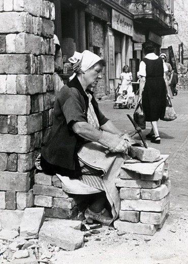Rubble Woman, a woman cleans bricks to sell, Berlin, Germany : Stock Photo