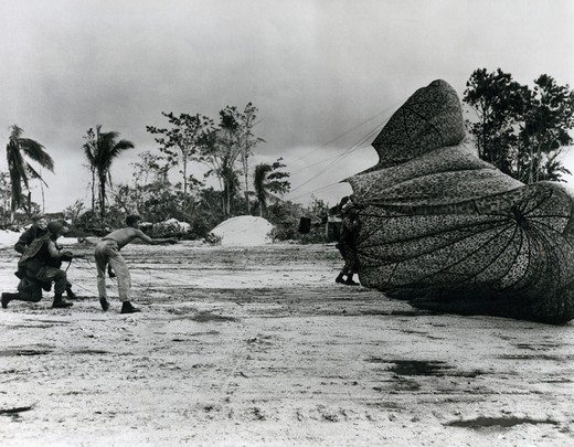 Stock Photo: 463-6103 American parachutist lands safely at the makeshift airstrip on Noemfoor Island, Papua, Indonesia, July 4, 1944