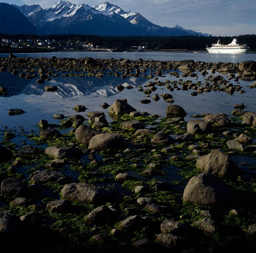 Mossy stones with a cruise ship in a canal, Lynn Canal, Alaska, USA : Stock Photo