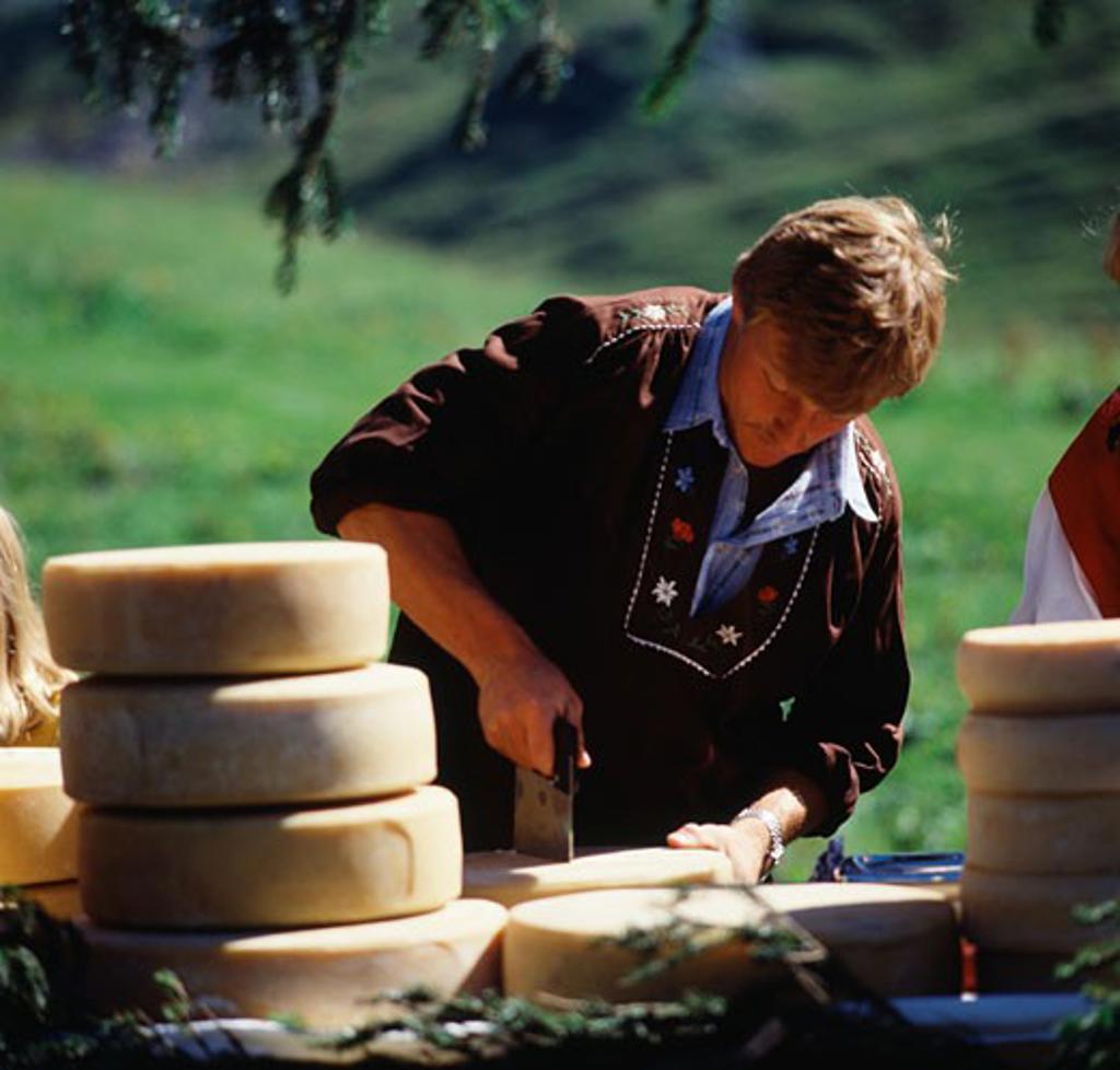 Stock Photo: 464-538 Cutting Cheese Hasliberg Bernese Oberland Switzerland