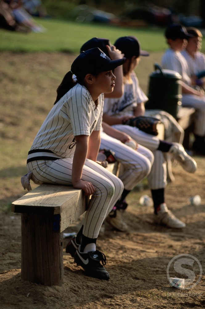 Stock Photo: 47-7389 Children sitting on a wooden bench at a baseball game