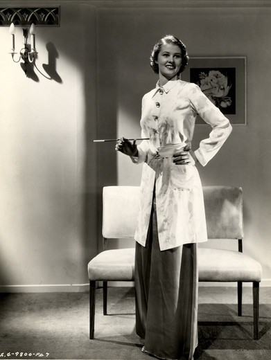 Stock Photo: 486-1732 Fashion model posing with cigarette holder in living room, 1931