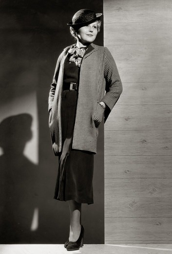 Fashion model posing by wall in autumn clothing, 1931 : Stock Photo