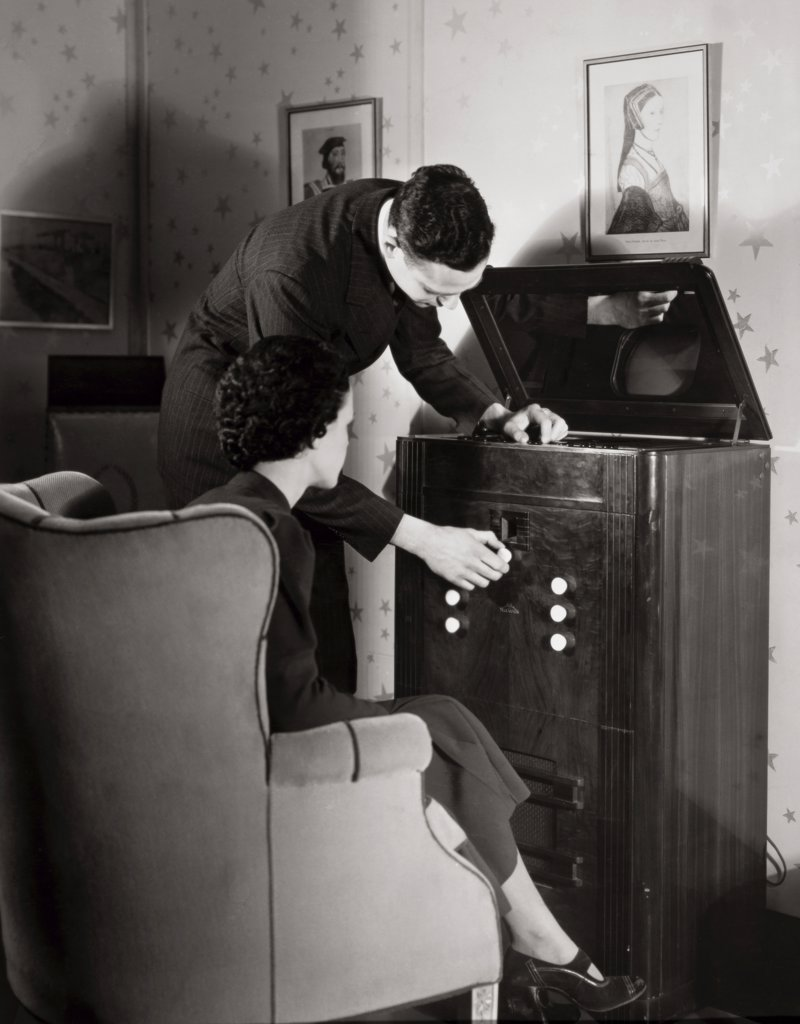 Young man operating a television in a living room, 1937 : Stock Photo
