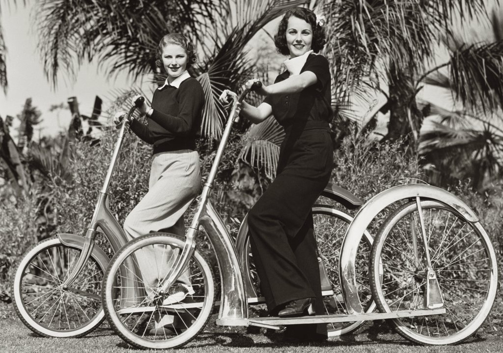 Stock Photo: 486-214 Portrait of two young women smiling with their bicycles