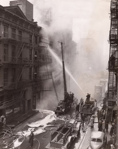 USA, New York State, New York City, Firemen Fighting Fire on 123 Mercer Street, More than 100 girls fled for their lives yesterday when a three-alarm tire swept through this 4-story loft building at 123 mercer St Although a fire house was only two doors away the girls, who work in a adjoining building took no chances. Three fireman w : Stock Photo