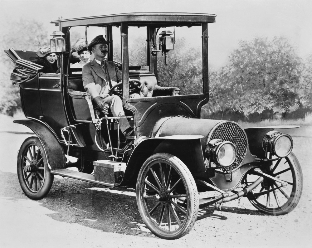 Stock Photo: 486-458 Mature man driving a car with two mid adult women sitting behind him, 1908 Franklin