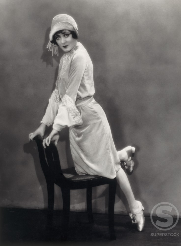 Stock Photo: 486-470 Portrait of a young woman leaning on a chair