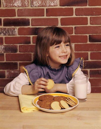 Girl holding a cookie and smiling : Stock Photo