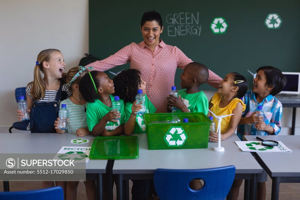 Stock Photo: 5512-17029850 Front view of happy schoolkids looking at teacher on desk in classroom of elementary school
