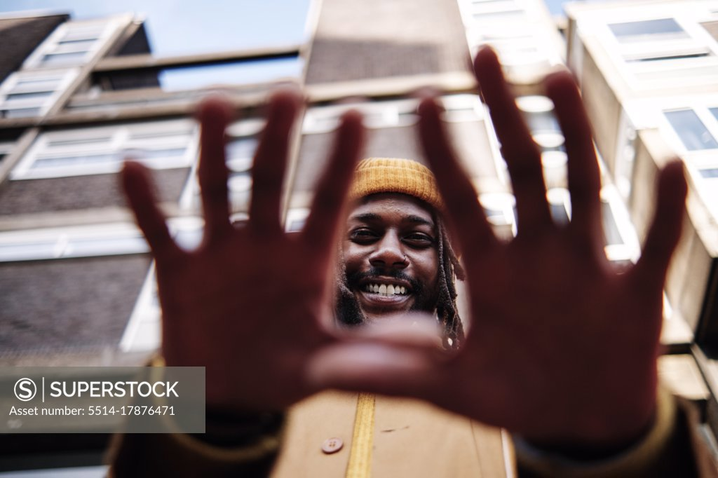 Stock Photo: 5514-17876471 young african guy smiling and gesturing with his hands while looking at camera. low angle shot.