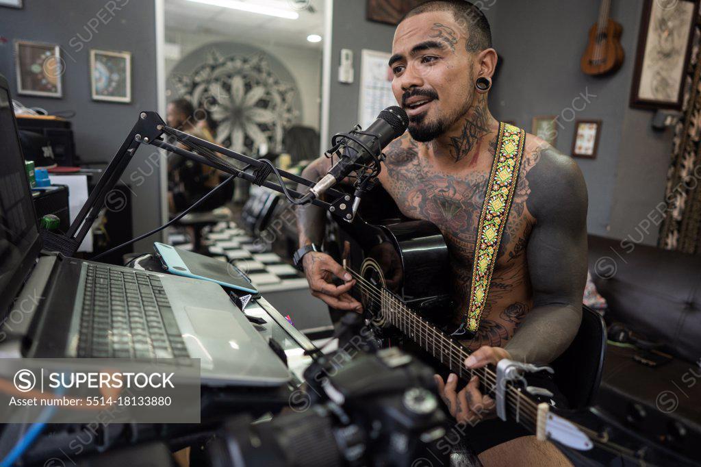 Stock Photo: 5514-18133880 Asian man recording in music studio.