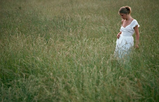 Side profile of a young woman walking in a field : Stock Photo