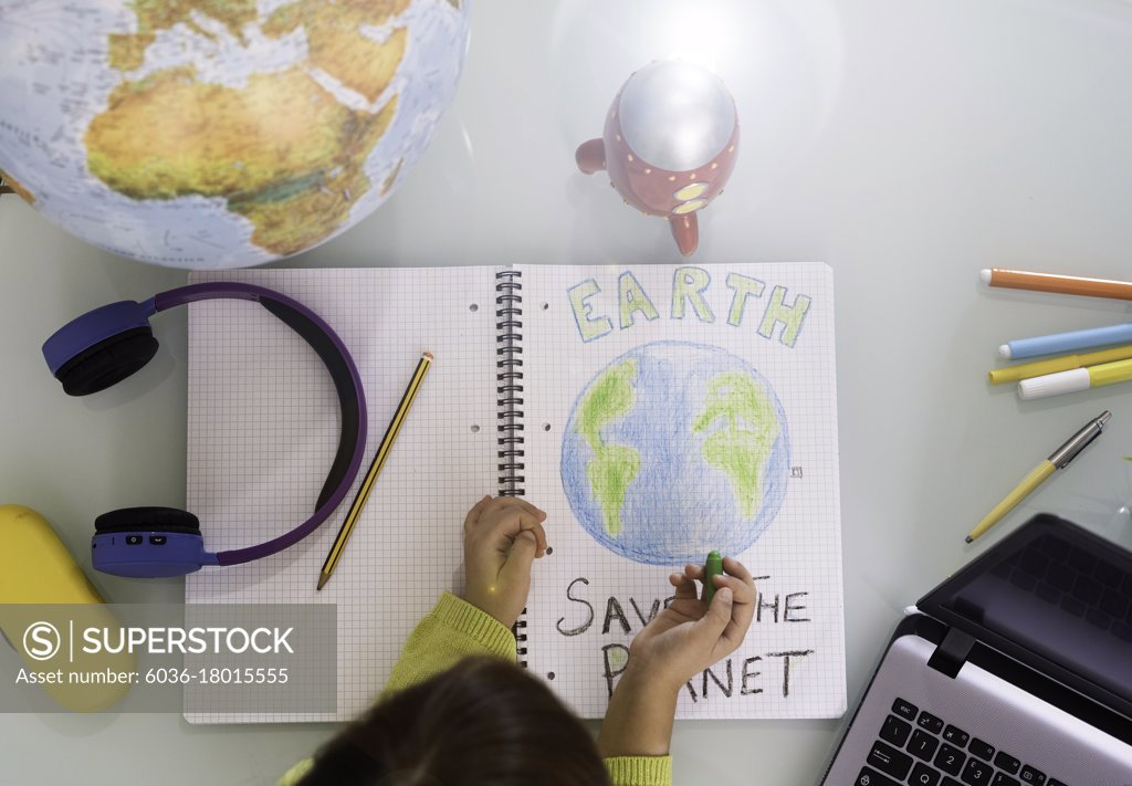 Stock Photo: 6036-18015555 Smiling child girl draws planet earth with wax colors on school notebook for Earth day - Little activist girl writes the message Save the Planet - Protection of environment, global warming - Top view