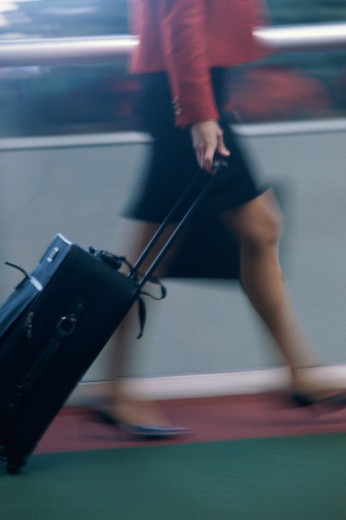Side profile of a woman pulling luggage : Stock Photo
