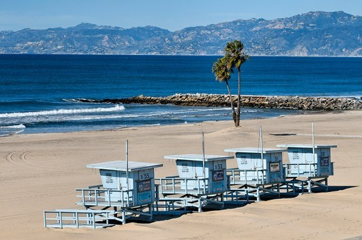 USA, California, Los Angeles, Westchester, Four lifeguard platforms gathered together on Dockweiler Beach during winter season, In distance Santa Monica Mountains rising above Santa Monica Bay as seen on clear winter day : Stock Photo