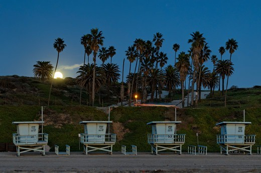 USA, California, Los Angeles, Westchester, Winter moonrise over Dockweiler Beach, where unused life guard booths have been placed together in waiting for summer season : Stock Photo