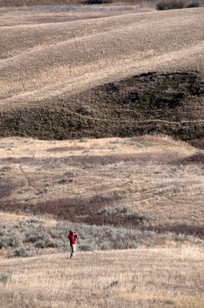 Stock Photo: 647-2127 Man hiking in a desert, Grasslands National Park, Saskatchewan, Canada