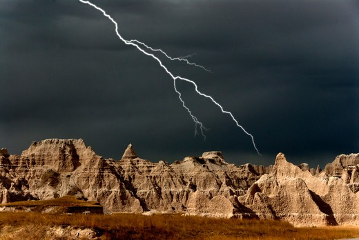 Storm clouds over eroded hills in badlands with lightning. South Dakota : Stock Photo