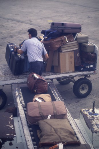 Man unloading luggage at an airport : Stock Photo