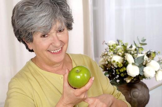 Stock Photo: 824-105071 ELDERLY PERSON EATING FRUIT. Model.