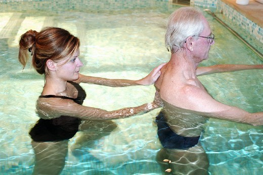 REHABILITATION, ELDERLY PERSON. REHABILITATION, ELDERLY PERSON Photo essay. Therapy pool at Dinan, in the Britanny region of France.   The sensation of weightlessness is the large advantage to re-education in a pool, thus facilitating the movement by alleviating stress to joints. Warm water (34°C) relaxes the muscles, the patient regains confidence by rediscovering ease of movement, and this flexibility is gradually integrated into daily activities. Pool re-education is principally indicat : Stock Photo