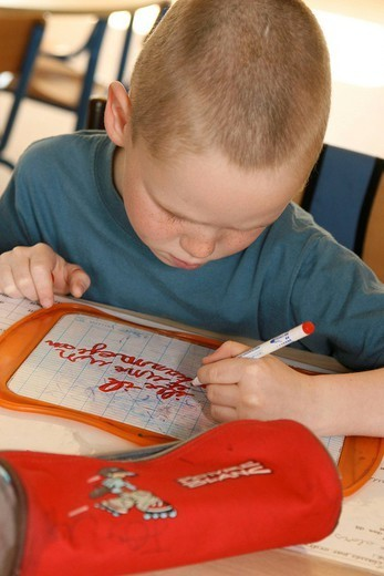 Stock Photo: 824-107776 SCHOOLCHILD. Primary school, class of 1st grade. Dictation of words to copy on a slate.