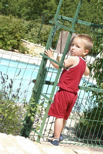 Stock Photo: 824-108793 ACCIDENT PREVENTION. ACCIDENT PREVENTION Model. 3 and 1/2 year-old boy. Pool is surrounded by fence to prevent accidents.