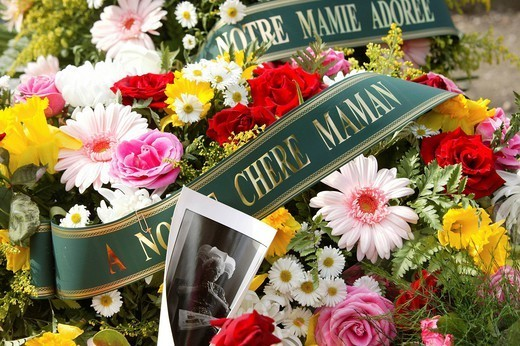CEMETERY. Flowers on tomb in Père Lachaise cemetery in Paris, France. Memory, photo, wreath. : Stock Photo