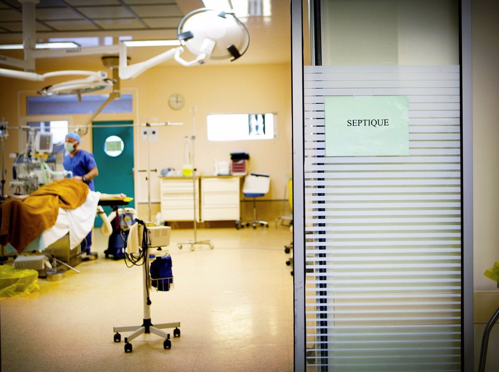Stock Photo: 824-114765 SEPTIC SURGERY. Reportage in the Osteoarticular Infections Referral Centre CRIOA at Diaconesses Croix Saint Simon hospital in Paris. Septic surgery, removing an internal fixation in the ankle following an infection. General anaesthetic.