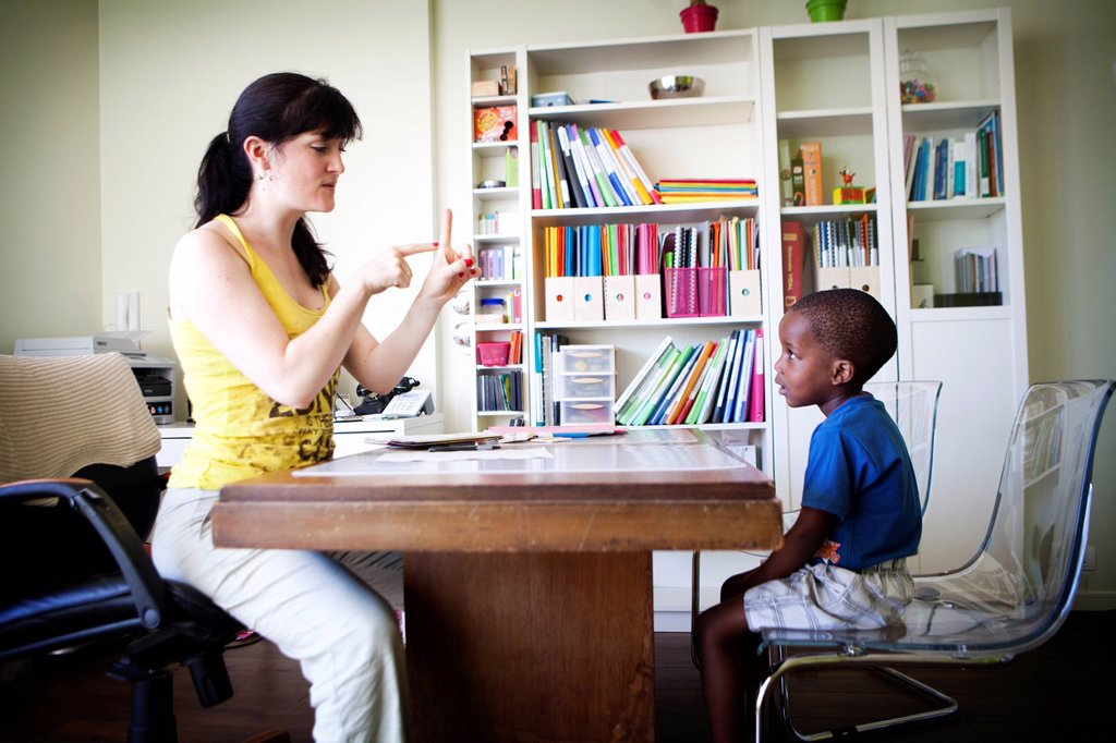 Stock Photo: 824-114925 CHILD IN SPEECH THERAPY. A feature shot at a speech therapist´s office in Noisy_le_Grand 93. Godwin, aged 3 years and 8 months, is given an assessment test. He is retarded in speech and language development as well as in understanding and expressing himself. The speech therapists uses the N_EEL language assessment test, which requires several sessions lasting between 2 and 3 hours. The therapist tests Godwin´s ability to name different parts of the body.