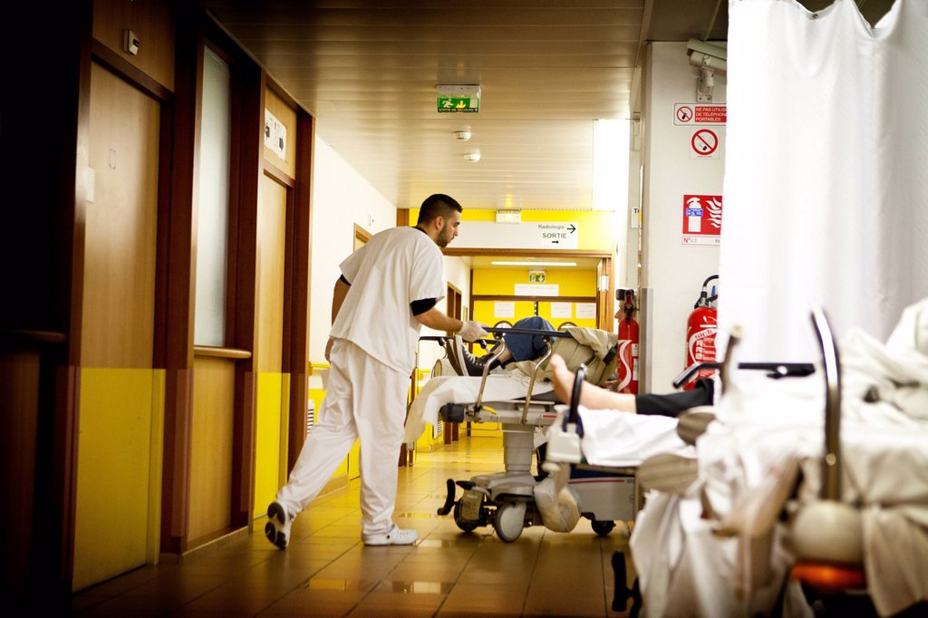HOSPITAL EMERGENCY. Reportage at night in the A&E department of Robert Ballanger general hospital, France. A stretcher bearer settles patients in the corridor. : Stock Photo