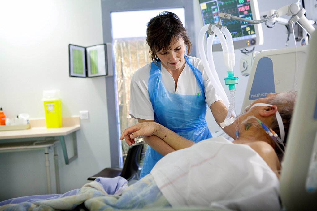 Stock Photo: 824-121177 Reportage in Robert Ballanger hospital's Intensive Care Unit in France. A physiotherapist exercises a patient.