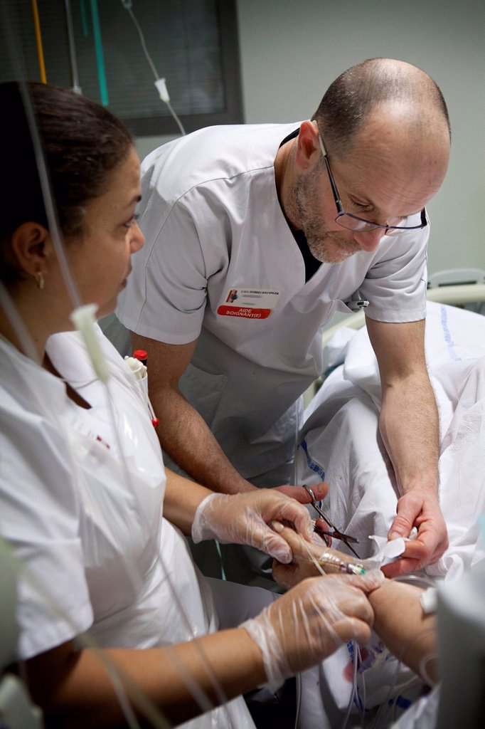 Stock Photo: 824-121217 Reportage in Robert Ballanger hospital's Intensive Care Unit in France. Two nursing auxiliaries place a dressing.